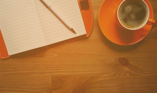 A pencil lying on top of an open notepad on the left. To the right, an orange mug and saucer. The mug has coffee in. All items are on a wooden coffee table.