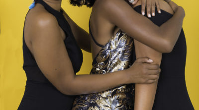 Three black femmes hugging against a yellow background. All are smiling.