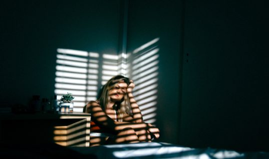 Girl sitting forlornly in a corner. Light through blinds casts a striped pattern on her.